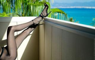 Dlouhé nohy v černých silonkách na balkóně nad mořem
