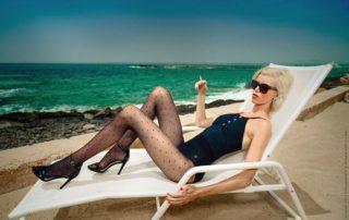 Modelka na pláži v černých silonkách s puntíky